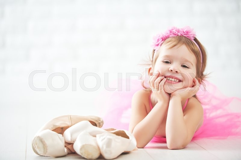 Little child girl dreams of becoming ballerina with ballet shoes and pointe shoes in a pink tutu skirt , stock photo