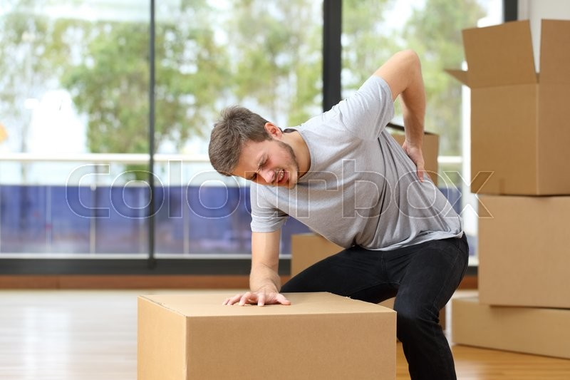 Man suffering back ache moving boxes in his new house, stock photo