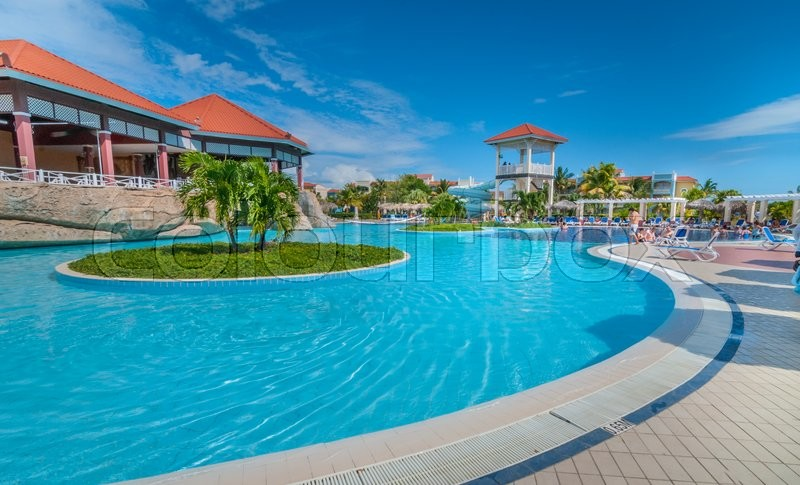 Hotel pool with people  Warm sunshine, inviting pool scene and deck chairs. People relaxing ...