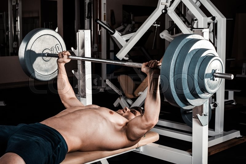 Muscular Man Doing Heavy Exercise. Athletic man pumping up muscles on bench press, stock photo