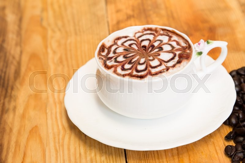 Milk foam coffee with flower pattern in a white cup on wooden background, stock photo