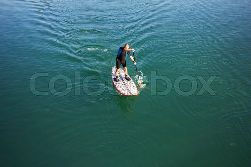 Stand up paddle board man paddleboarding on tranquil lake, stock photo