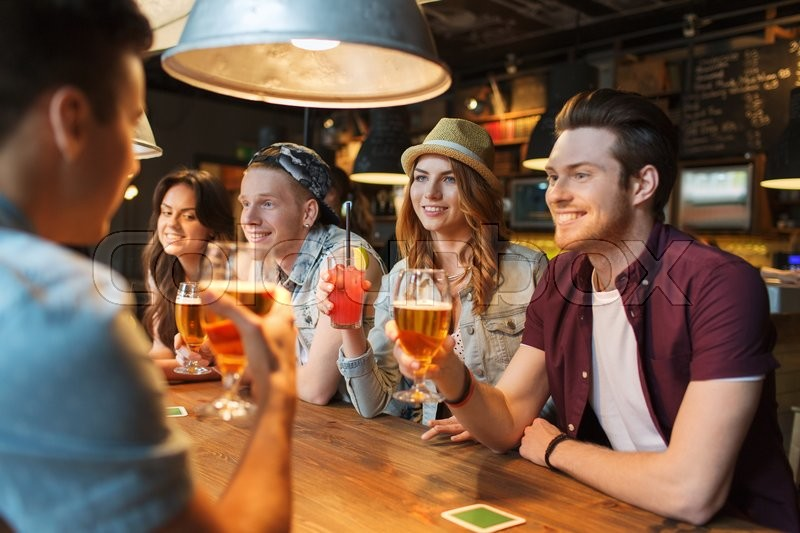 People, leisure, friendship and communication concept - group of happy smiling friends drinking beer and cocktails talking at bar or pub, stock photo