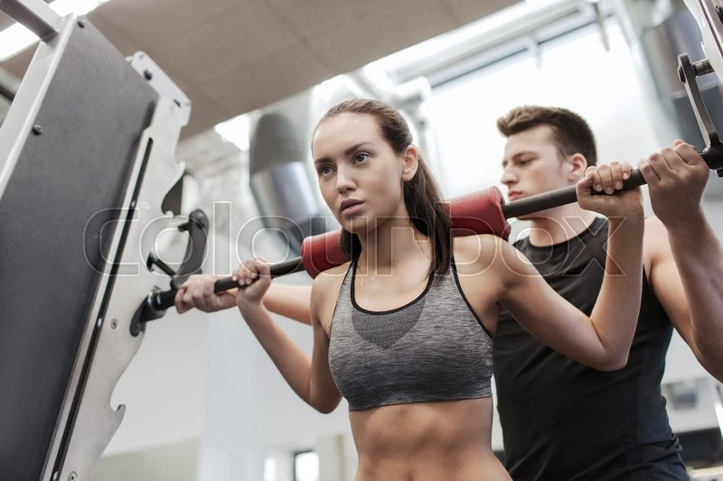 Sport, fitness, teamwork, weightlifting and people concept - young woman and personal trainer with barbell flexing muscles in gym, stock photo