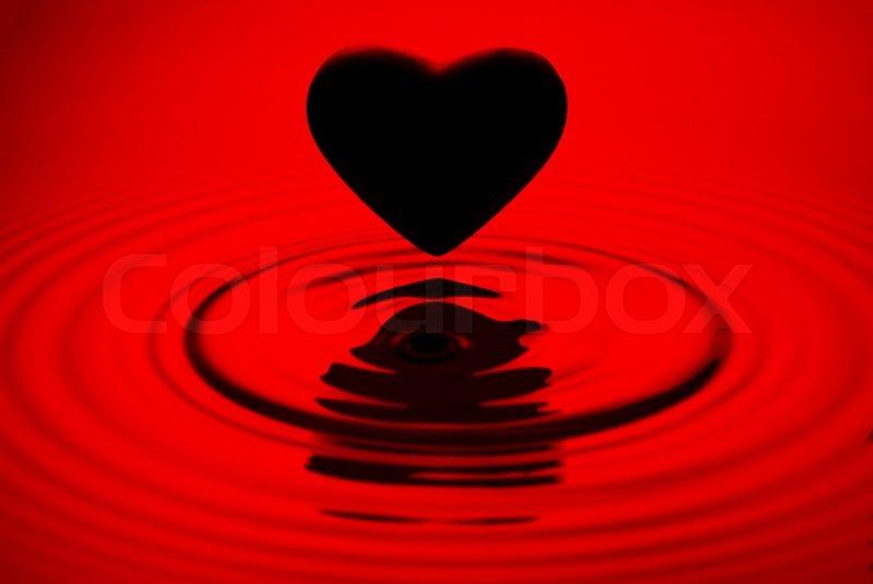 Black heart siluett over red water ... | Stock Photo ...