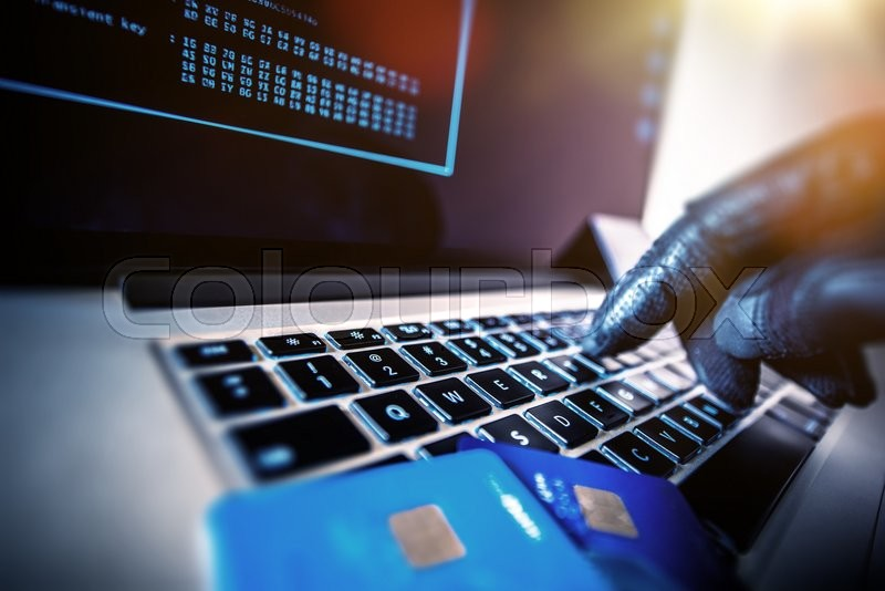 Credit Cards Theft Concept. Hacker with Credit Cards on His Laptop Using Them For Unauthorized Shopping. Unauthorized Payments, stock photo