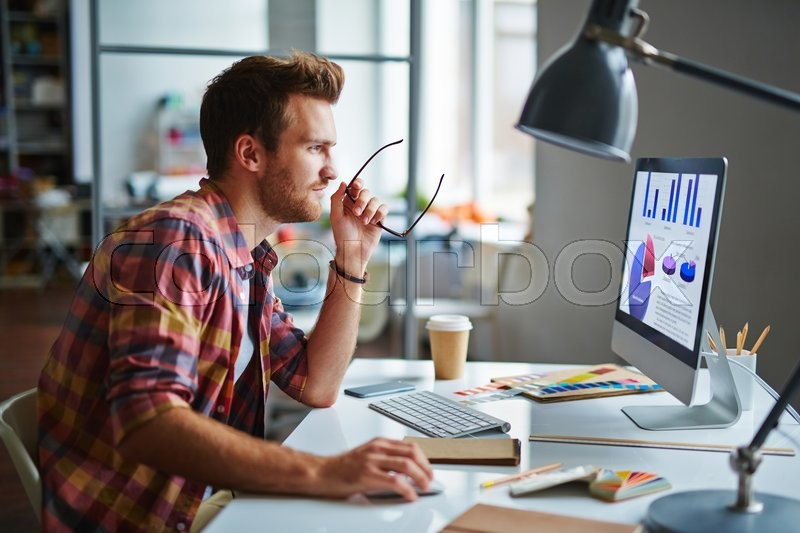 Man as a designer sitting at his table and working on computer, stock photo