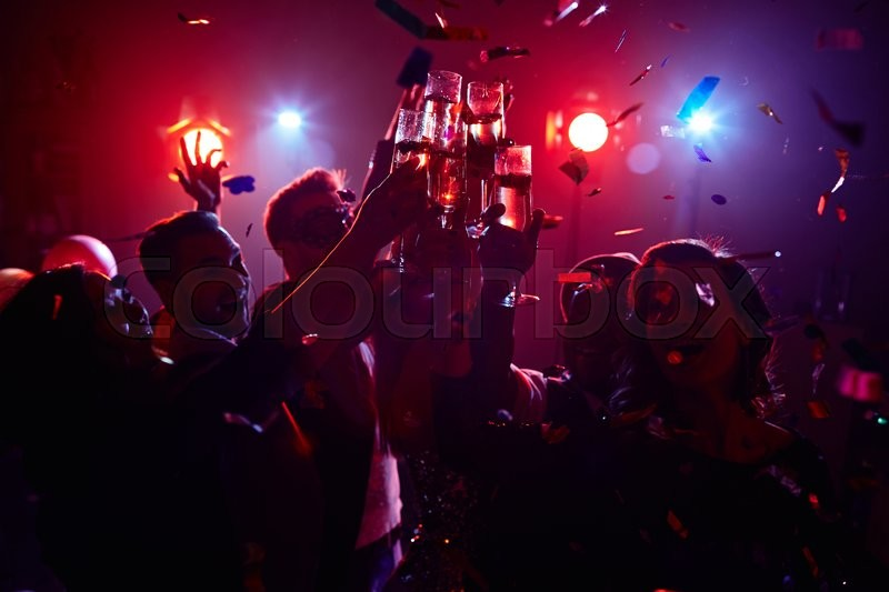 Young friendly people toasting in night club, stock photo