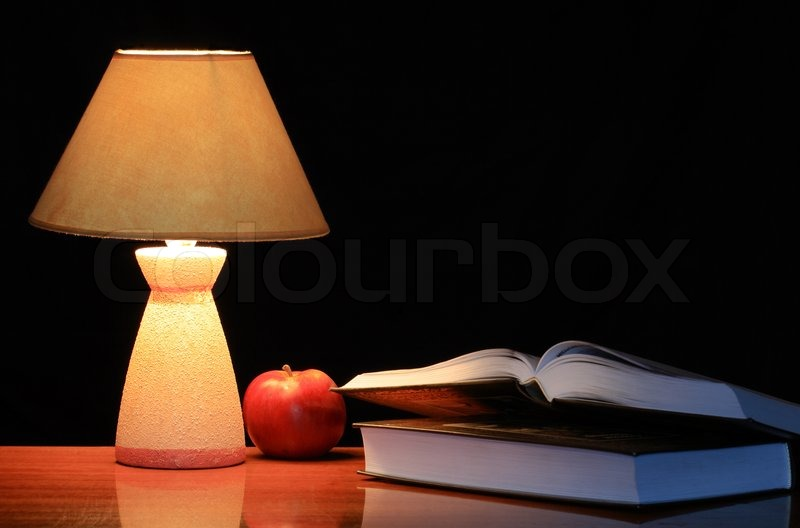 Luminous Lamp Standing On The Table Near Red Apple And Two Books On Dark  Background With Copy Space, Stock Photo