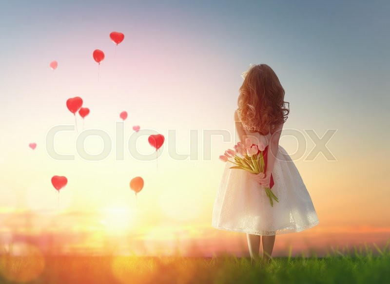 Sweet child girl looking at red balloons. Little child girl holding bouquet of flowers. Balloons in shape of heart flying in the sunset sky. Wedding, Valentine, love concept. , stock photo