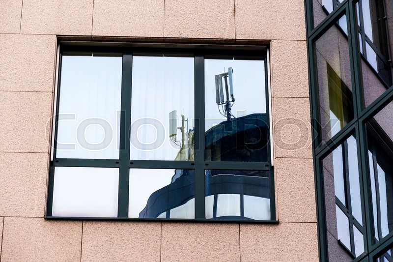 The mobile radio transmitter of a mobile operator\'s reflected in a window. mobile transmitters and electromagnetic pollution, stock photo