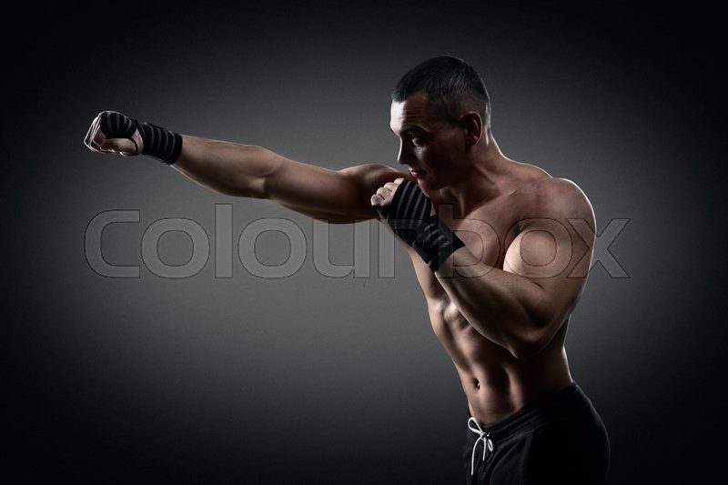 Fighter boxer standing staring strong on black background. Young masculine caucasian male athlete, stock photo
