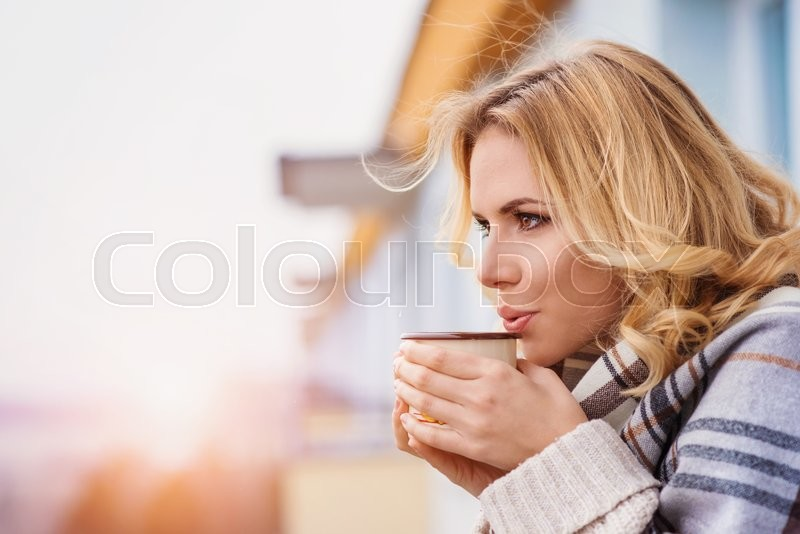 Beautiful woman relaxing at home with cup of coffee, stock photo