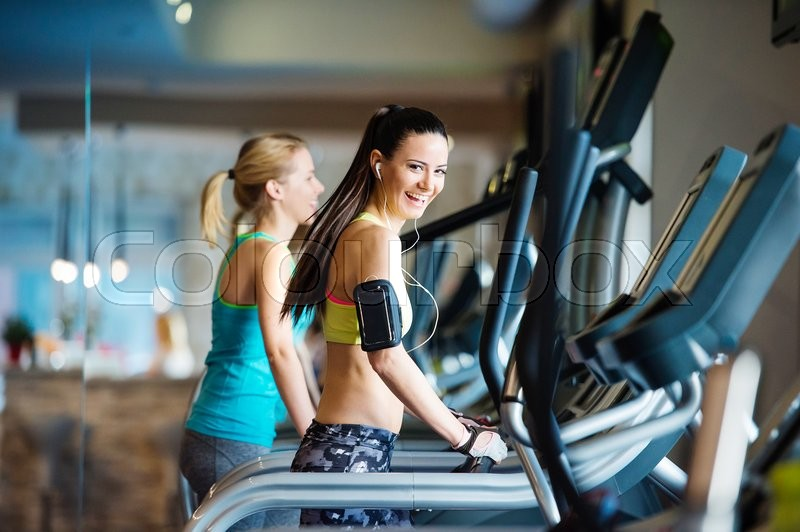 Two young beautiful women working out in gym, stock photo
