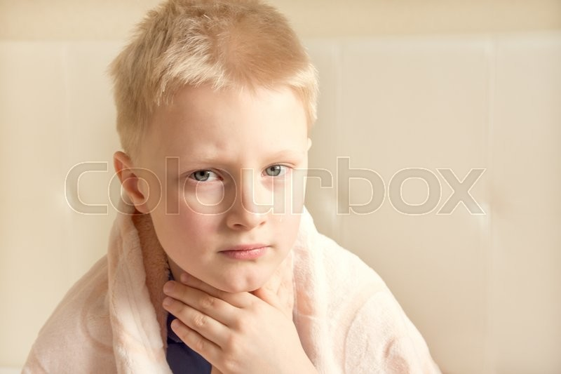 Sick and sad child (boy, kid, teen) wrapped in blanket, stock photo