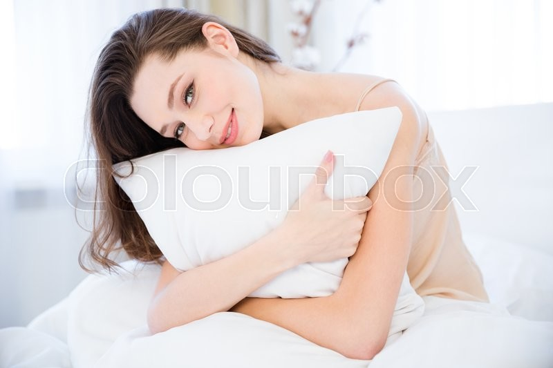 Happy beautiful relaxed young woman hugging pillow on bed in bedroom , stock photo