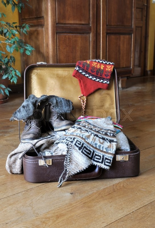 062c2aa7fac Open suitcase full of warm clothes on ...