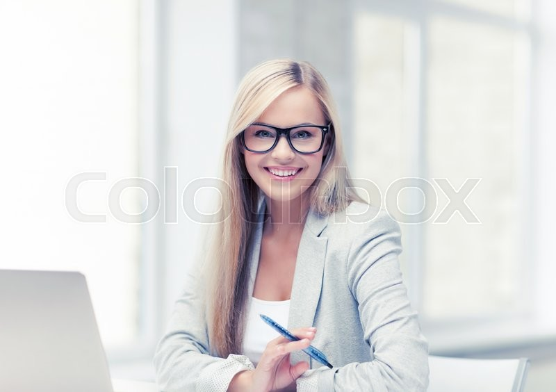 Indoor picture of smiling woman with laptop and pen, stock photo