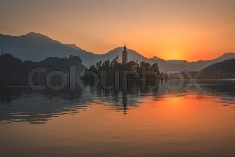 Little Island with Catholic Church in Bled Lake, Slovenia at Beautiful Colorful Sunrise with Castle and Mountains in Background, stock photo