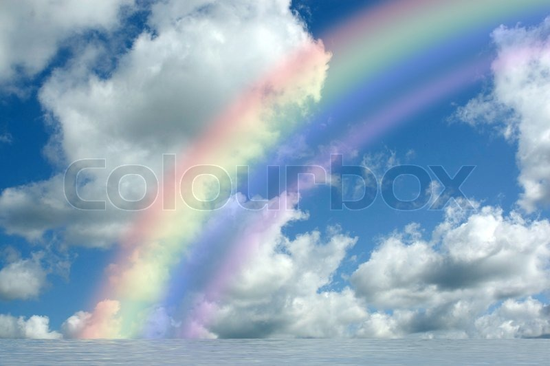 White Fluffy Clouds With Rainbow In The Blue Sky Stock