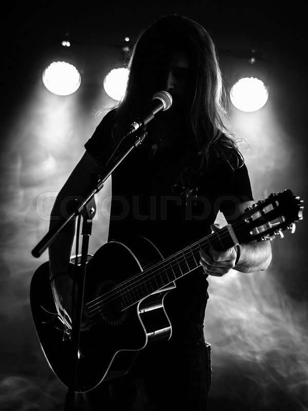 Photo Of A Backlit Young Man With Long Hair In Silhouette Playing An