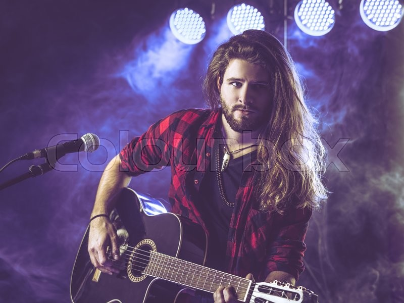 Photo Of A Young Man With Long Hair And A Beard Playing An Acoustic