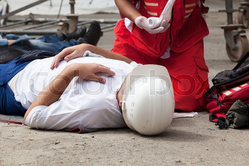 Workplace accident - First aid after occupational injury, stock photo