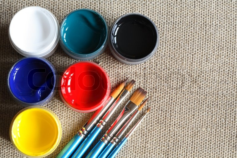 set of paintbrushes and color paint on canvas background stock