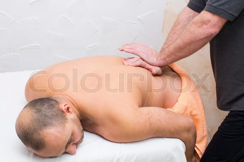 Man doing sports massage at the massage parlor, stock photo