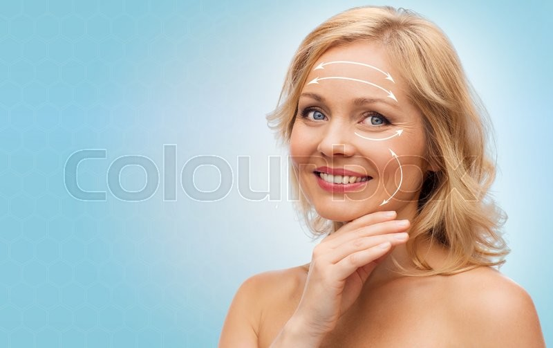 Beauty, people, anti-aging and skincare concept - smiling woman with bare shoulders touching face over blue background, stock photo