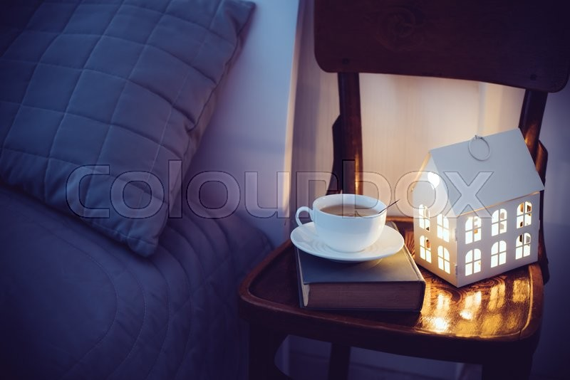 Cozy evening bedroom interior, cup of tea and a night light on the bedside table. Home interior decor with warm light, stock photo