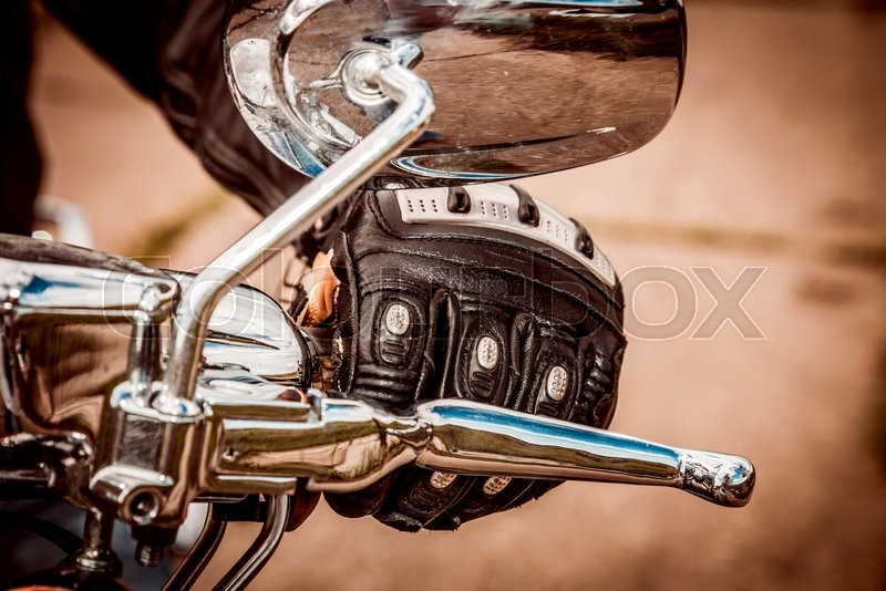 Human hand in a Motorcycle Racing Gloves holds a motorcycle throttle control. Hand protection from falls and accidents, stock photo
