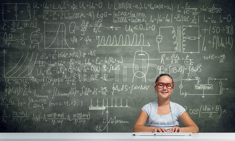 Girl of school age in red glasses sitting at table and typing on keyboard, stock photo