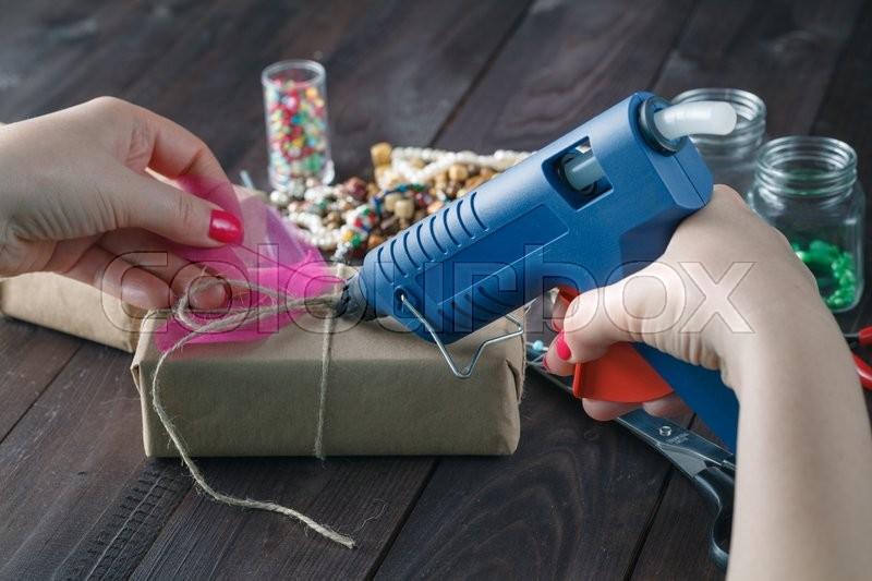 Prepare birthday concept. Woman glue gift box, stock photo