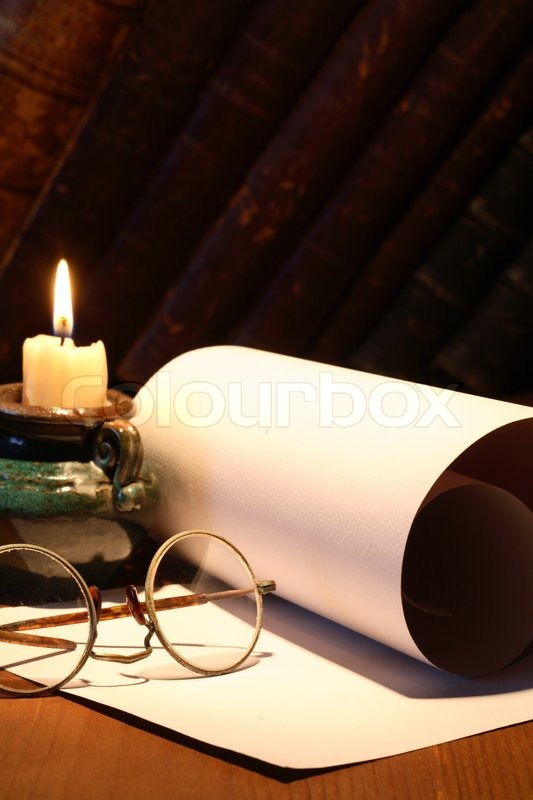 scroll and old spectacles near lighting candle on dark