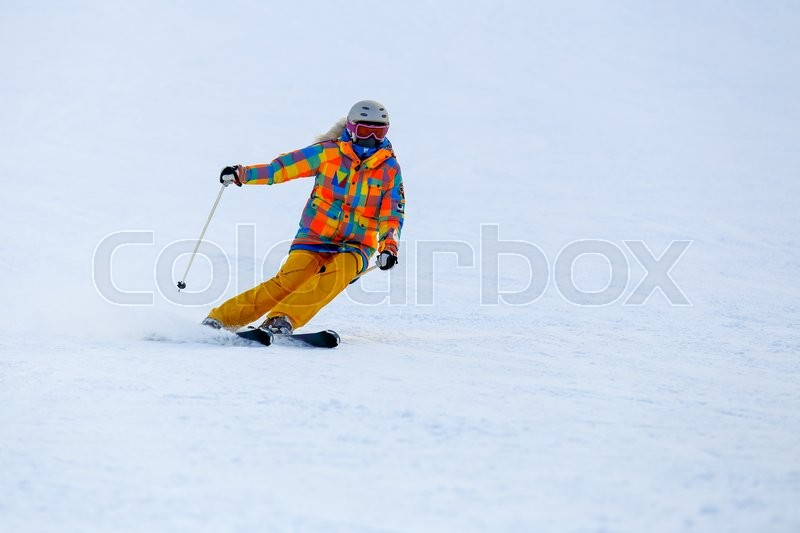 Male skier skiing in fresh snow on ski slope on a sunny winter day at the ski resort. Skier in red ski suit and mask slides fast while skiing from slope, stock photo