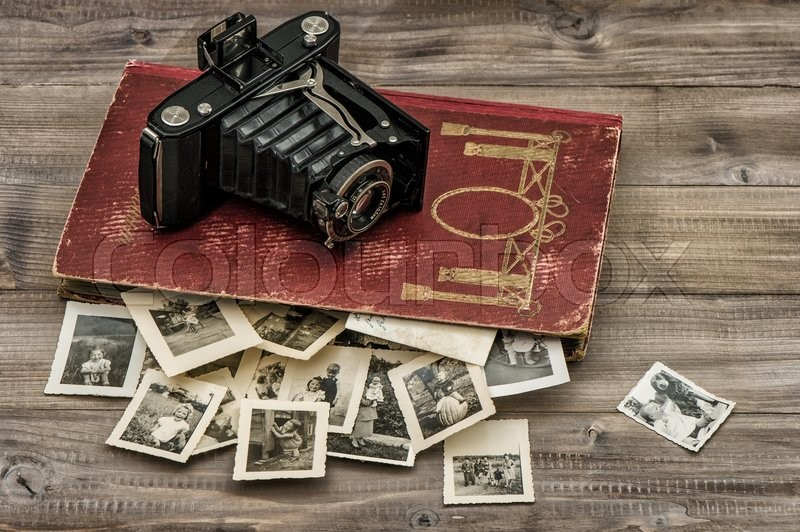 Antique film camera and photo album with old pictures on wooden table, stock photo