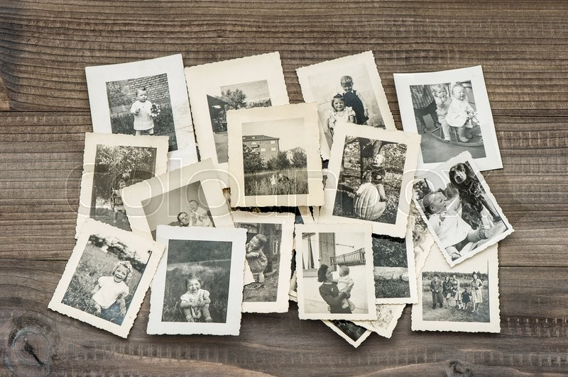 Old family photos on wooden table. Vintage pictures , stock photo
