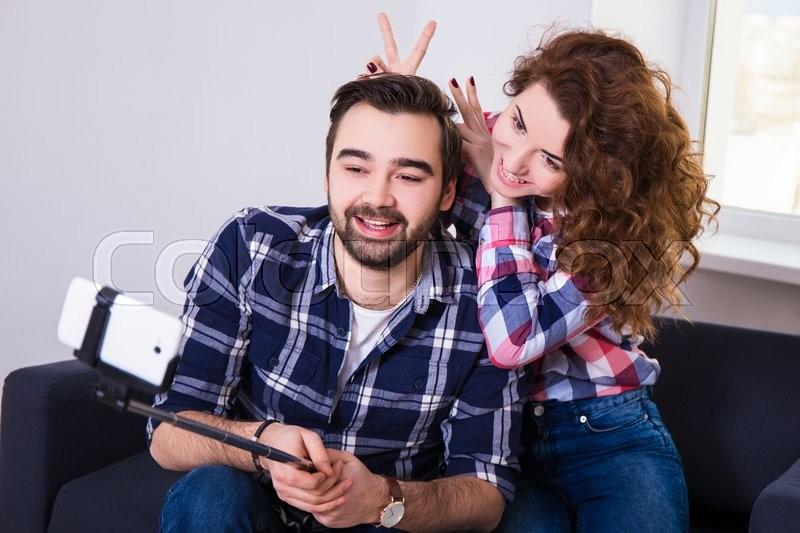Happy funny couple taking photo with cell phone on selfie stick, stock photo