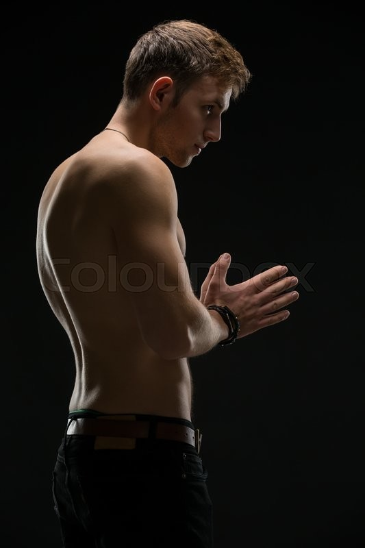 Stock image of 'Relief man with a naked torso and black pants. In the studio on a black background. Hands are closed in front of his hands. Vertical photo'