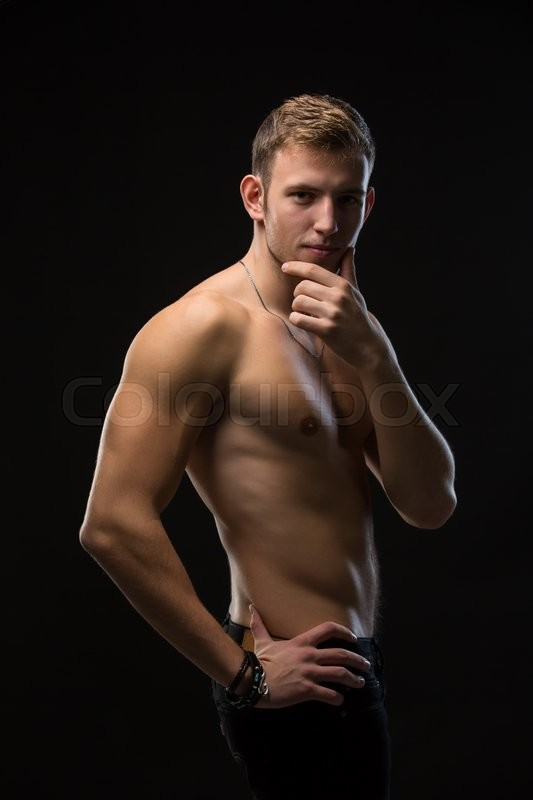 Stock image of 'Sensual young man with perfect athletic body. The black pants with a naked torso. Thoughtfully rubbing his chin. Vertical photo'
