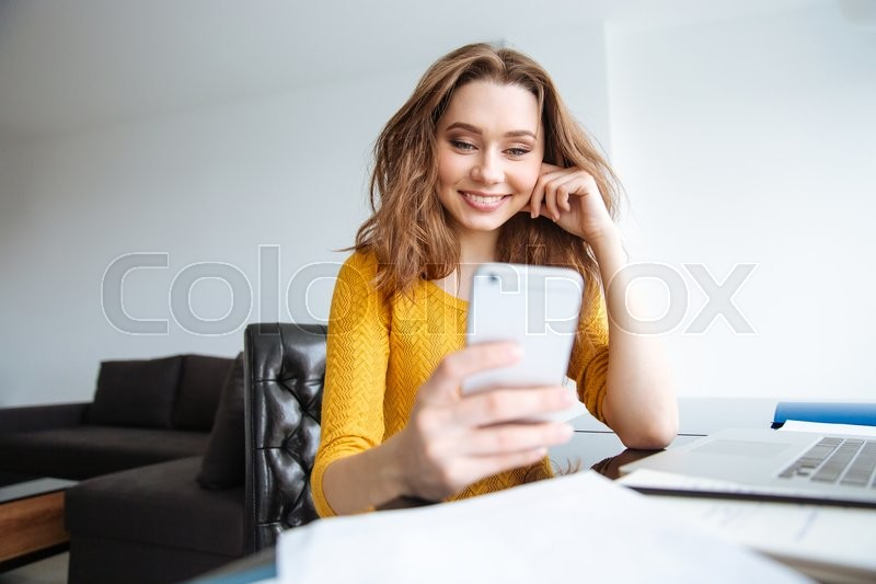 Stock image of 'Smiling young woman sitting at the table with laptop and using smartphone at home'