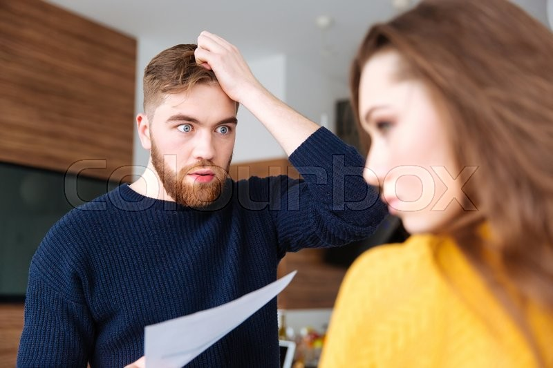 Stock image of 'Angry man discussing about domestic bills with her wife at home'