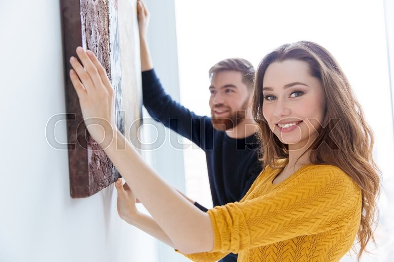 Stock image of 'Cheerful couple hanging picture on the wall at home'