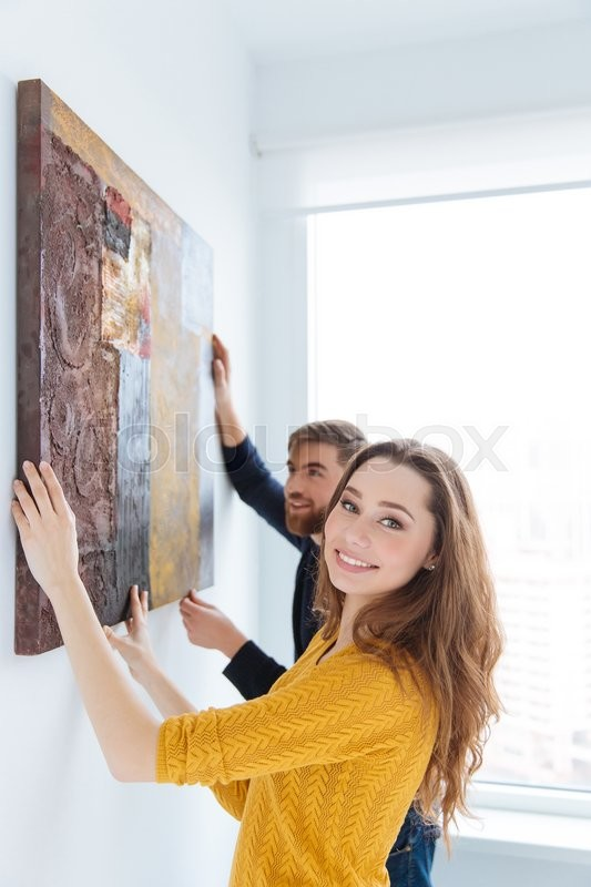 Stock image of 'Smiling couple hanging picture on the wall at home'