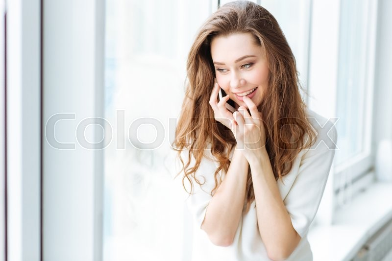 Stock image of 'Smiling woman talking on the phone and looking in window'