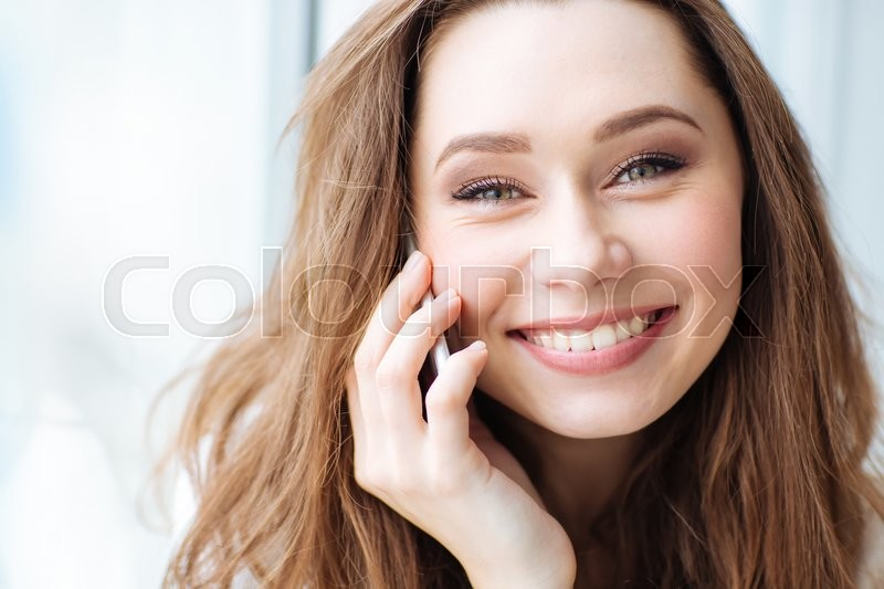 Stock image of 'Closeup portrait of a smiling woman talking on the phone and looking at camera'