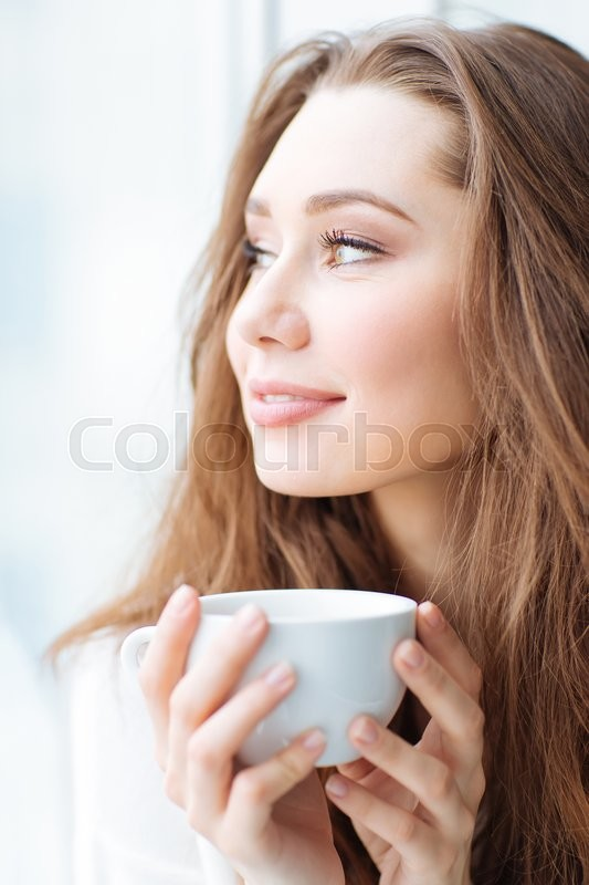 Stock image of 'Charming happy young woman drinking coffe and dreaming'