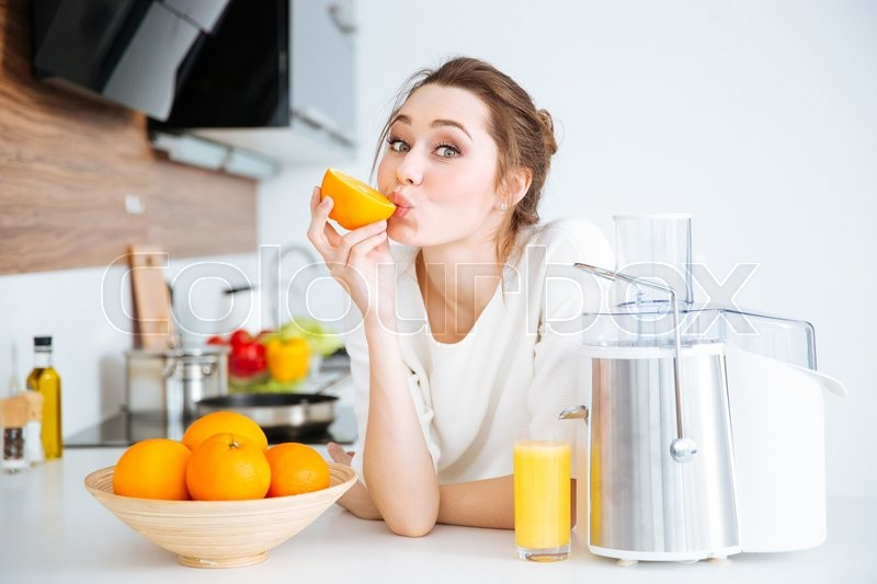 Cute charming young woman making juice and eating oranges on the kitchen, stock photo