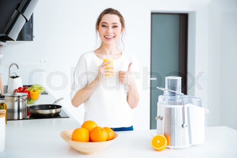 Stock image of 'Cheerful charming young woman drinking juice and showing thumbs up at home'